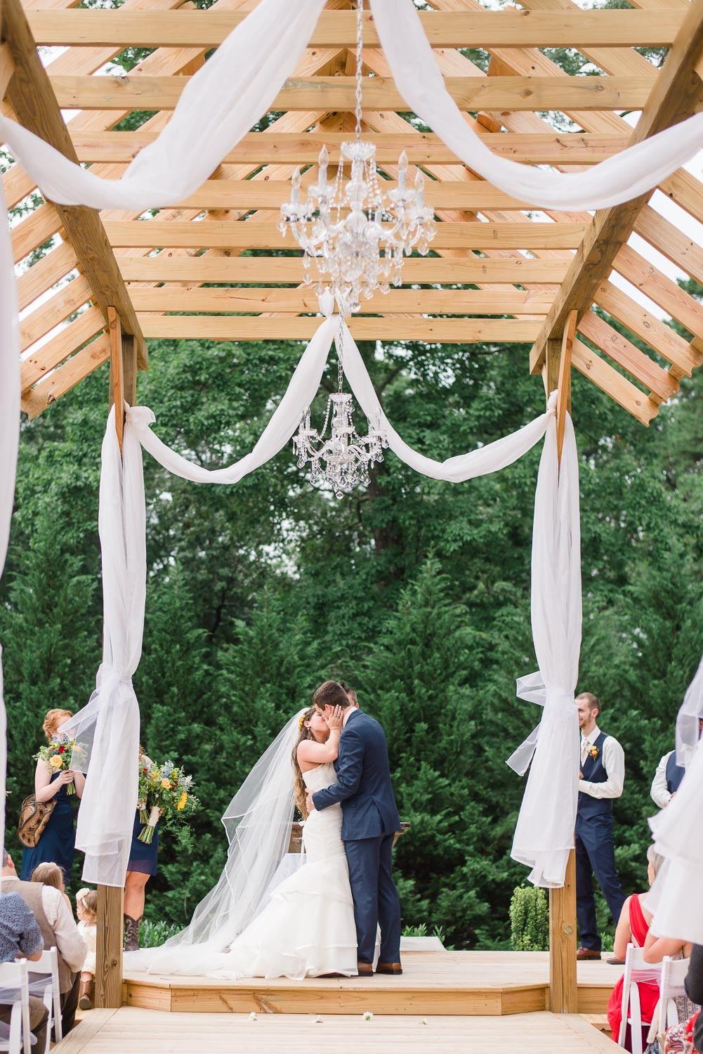 outside wedding ceremony with white drapes and chandeliers
