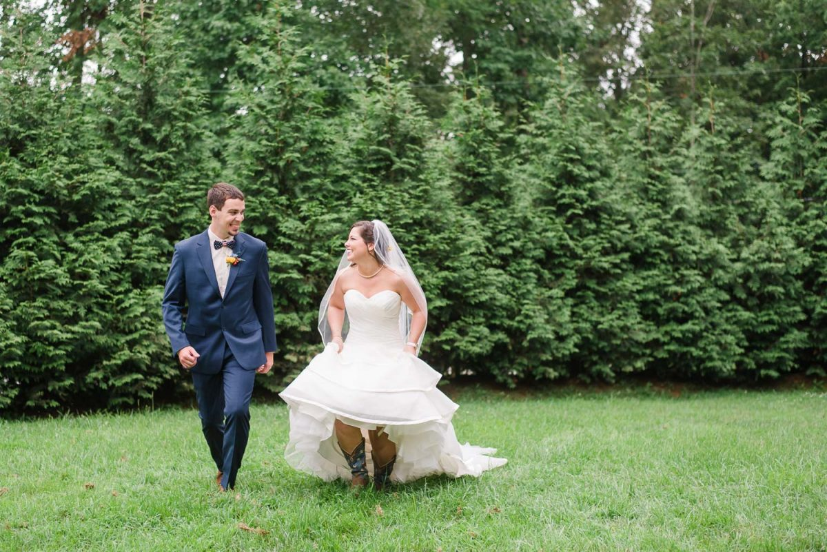 bride running in cowboy boots and wedding dress. Groom in navy blue suit