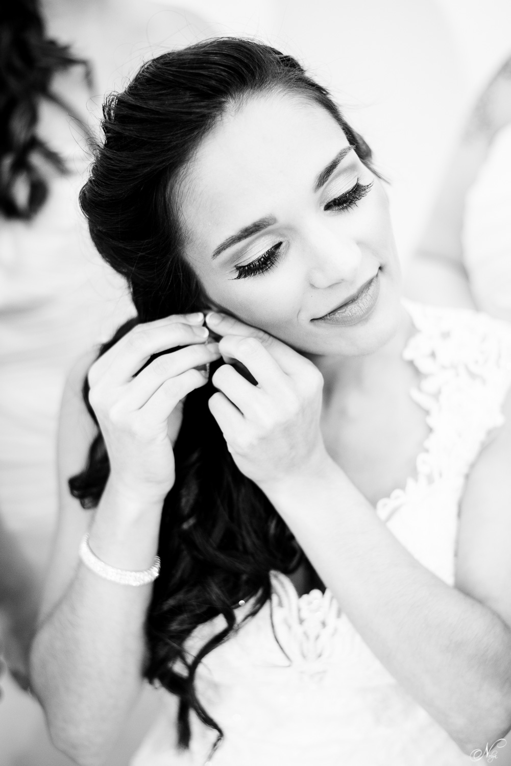 bride with long dark hair putting on earrings