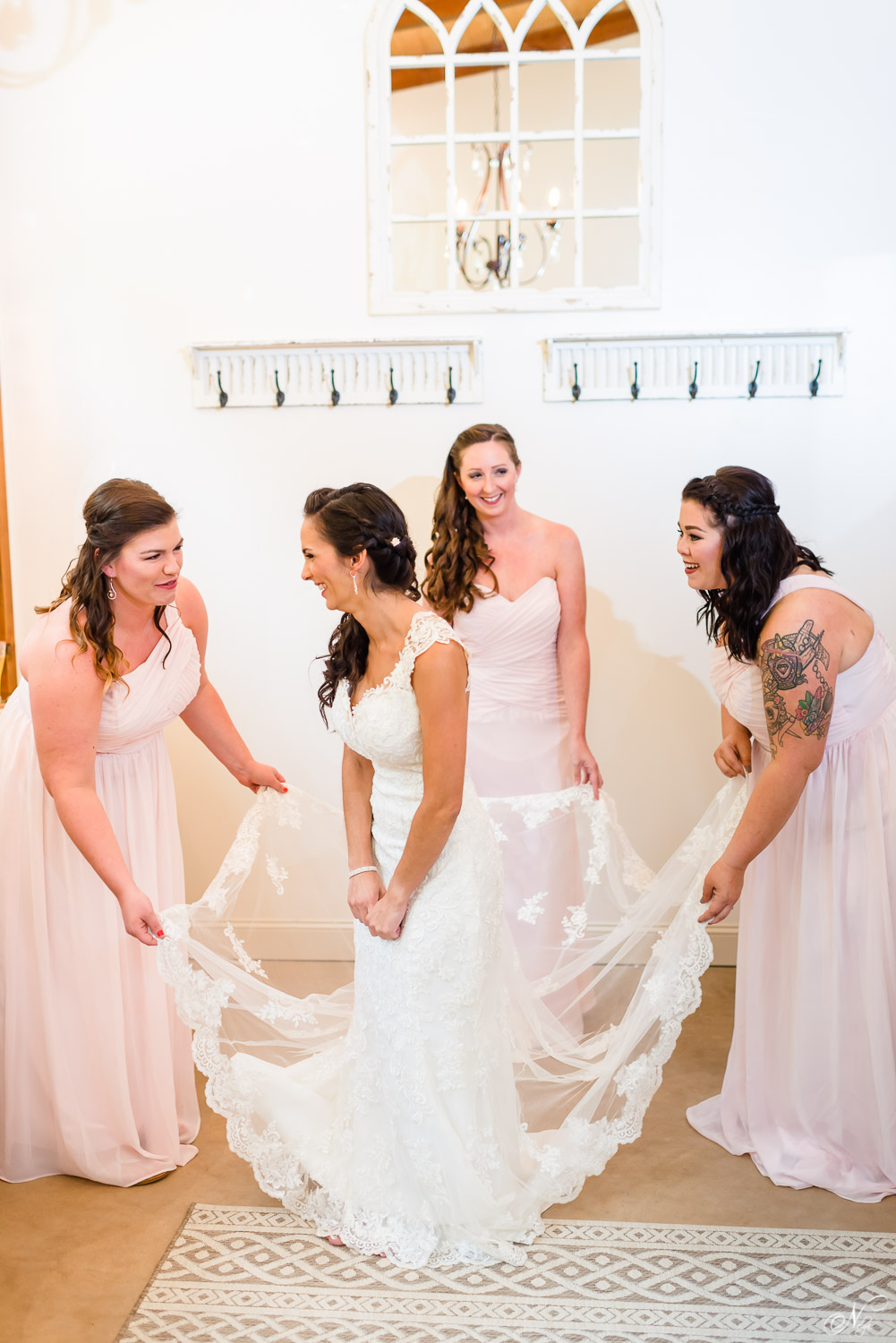 bridesmaids helping bride adjust her dress