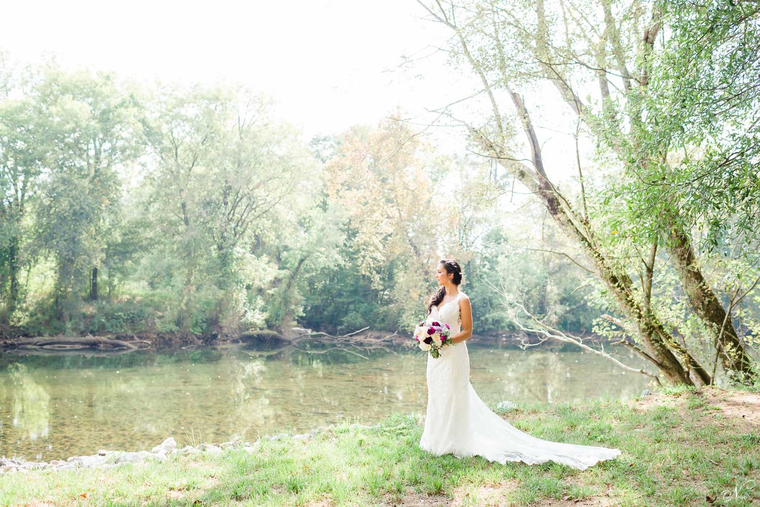 bride standing on the edge of the river in front of Hiwassee River weddings venue