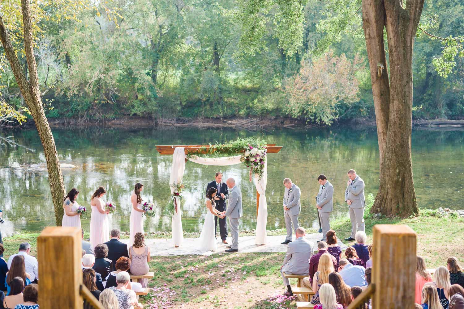 prayer at start of river front wedding ceremony in front of Hiwassee River Weddings
