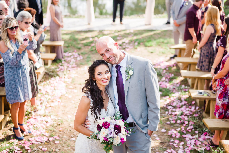 bride and groom just married walking up pink rose petal path