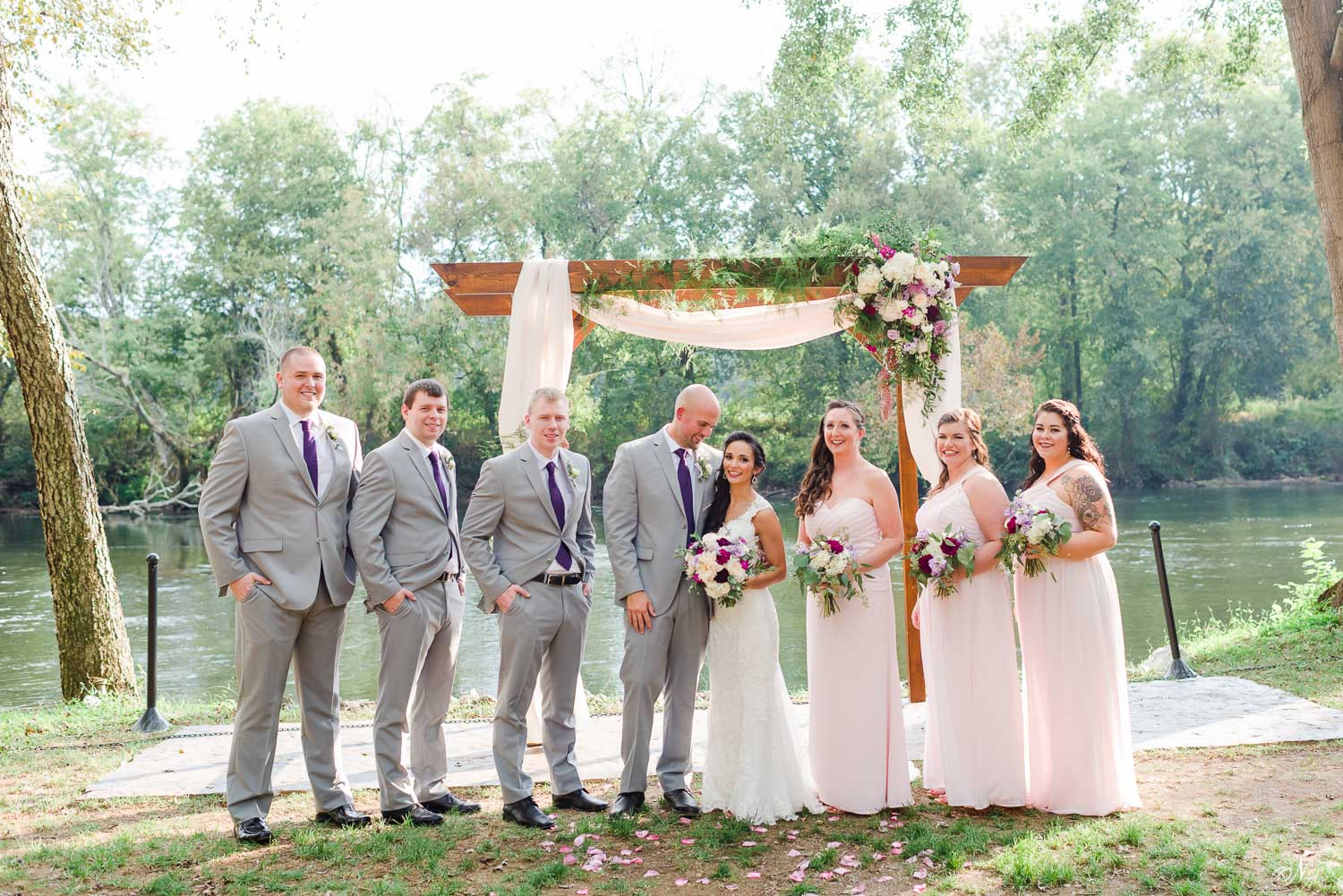 wedding party in front of wedding arch on hiwassee river