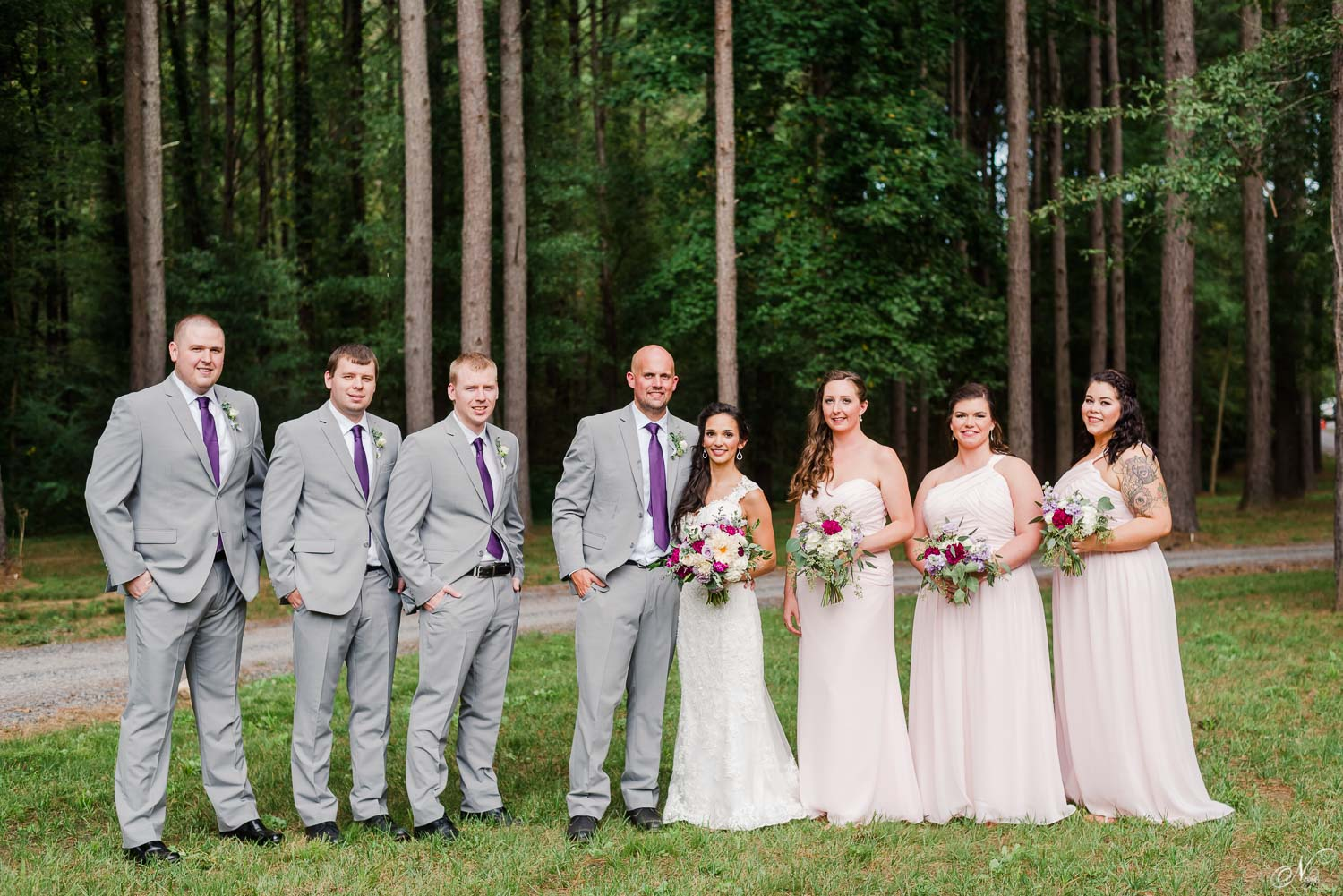 wedding party with pine trees in background