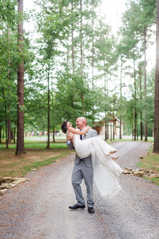 groom picking up bride onwindy road of Hiwassee River weddings
