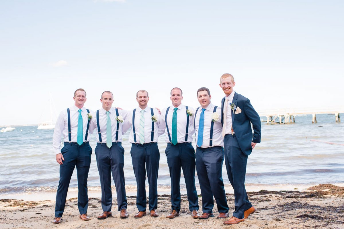 groomsmen in navy blue suspenders on the beach