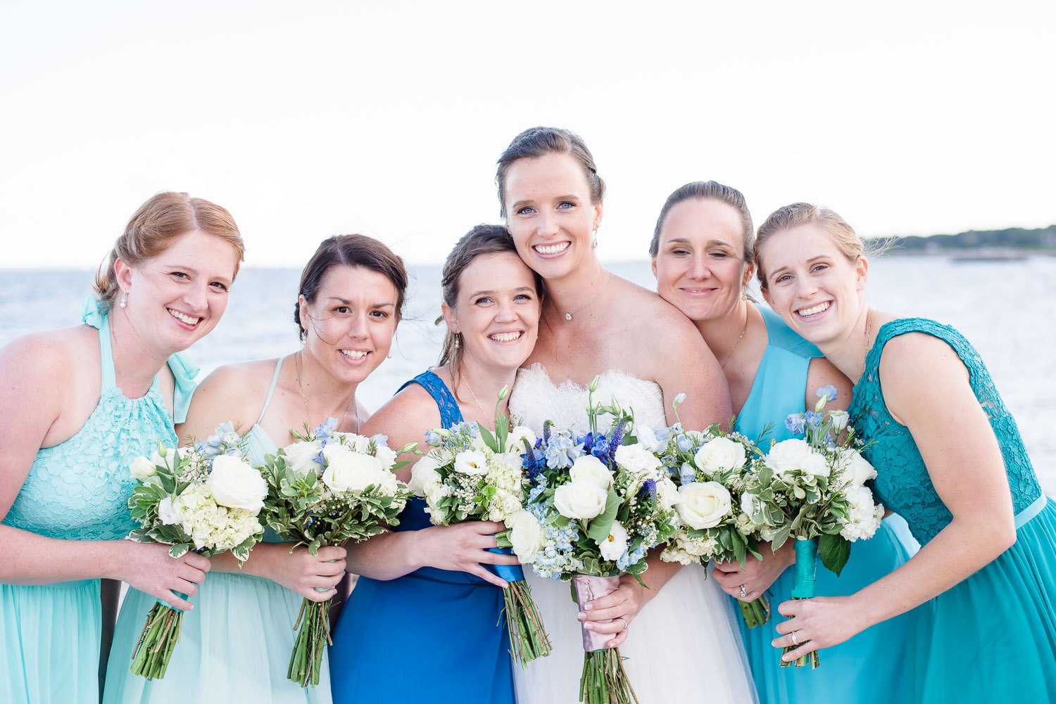 bride and bridesmaides with larkspur, hydrangea and white rose bouquets