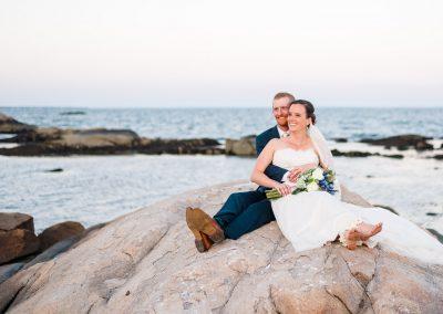 wedding photographer takes wedding couple out onto rocks for sunset photos