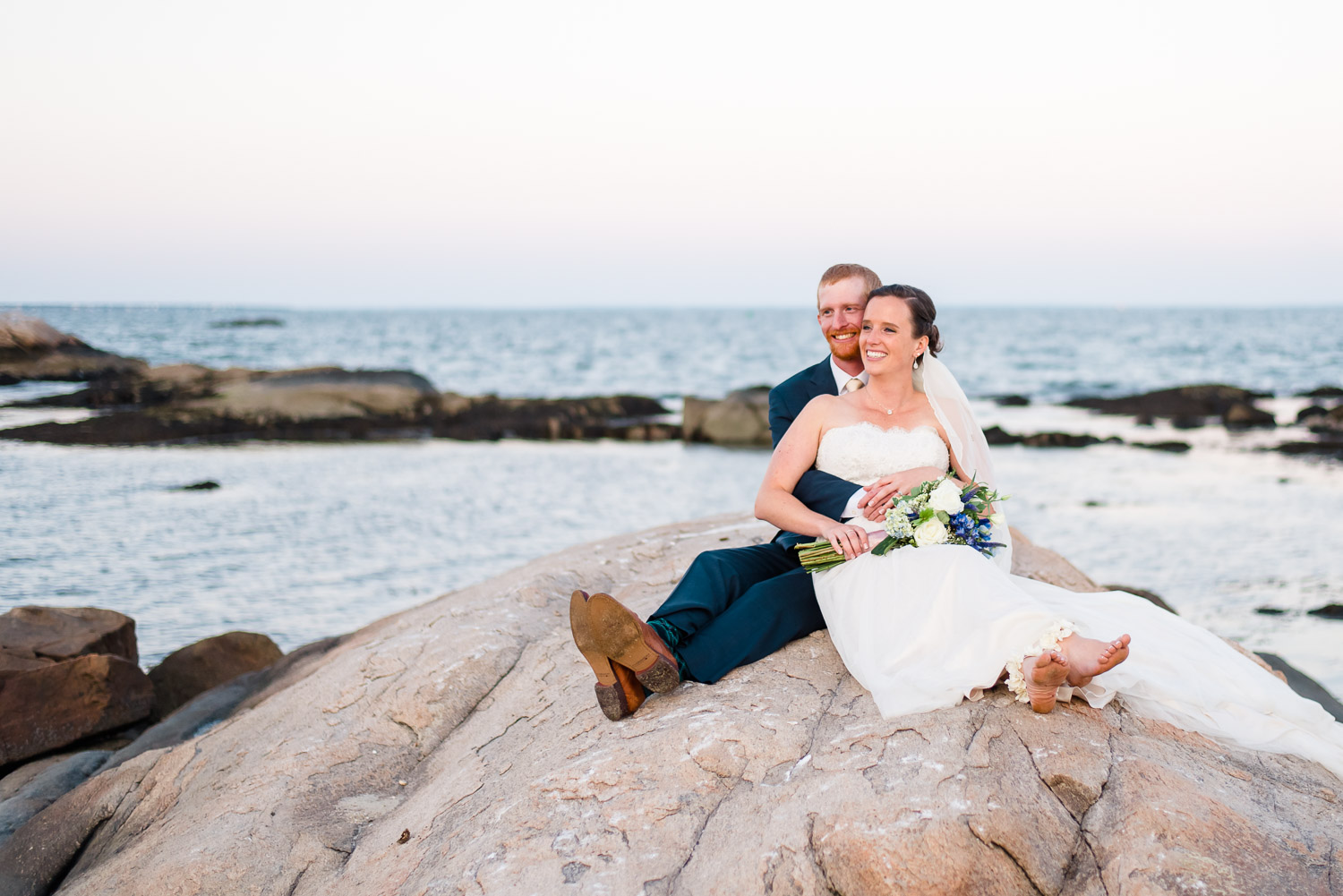 wedding photographer takes wedding couple out onto rocks for sunset photos