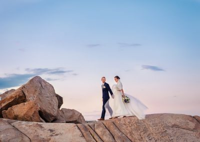 bride and groom walking as the wind catches her dress at sunset
