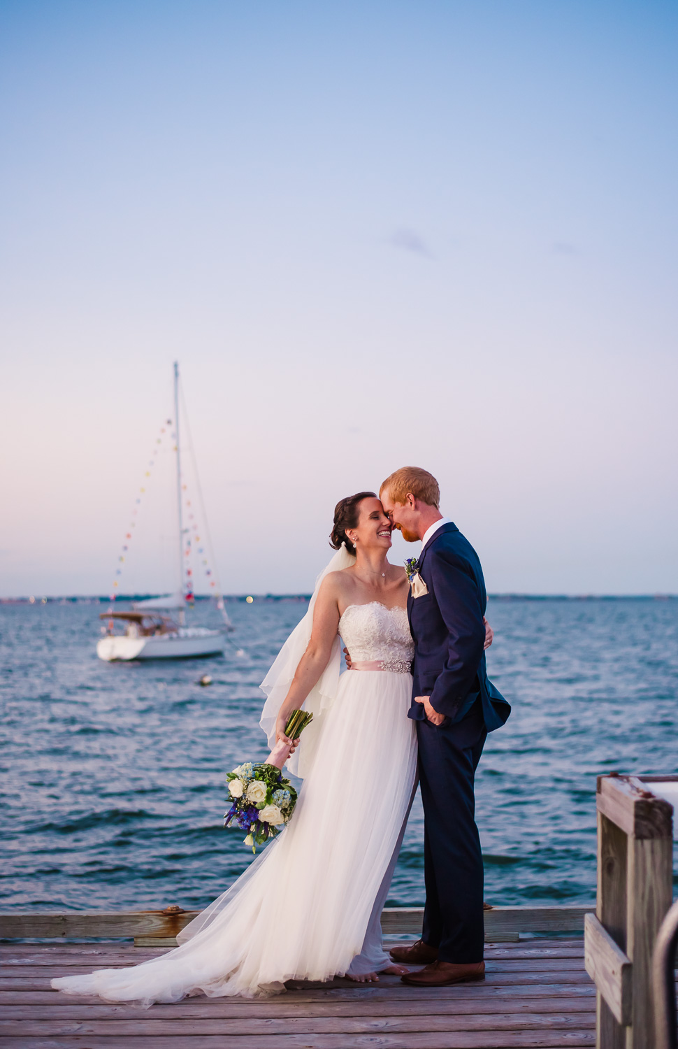 new mrs and mr stop to kiss on dock with honeymoon boat in background