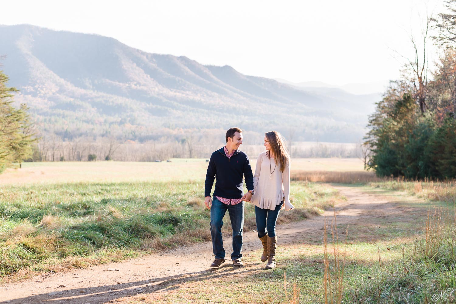 couple walking up trail laughing in cades cove in tennessee
