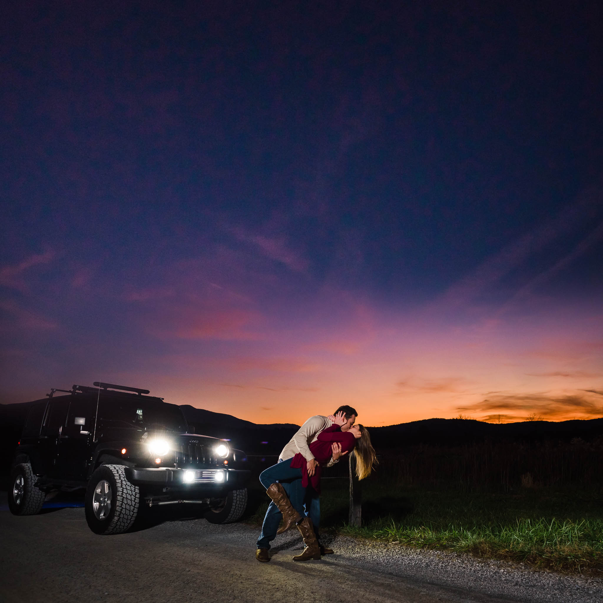jeep with headlights on in front of a killer sunset with couple kissing