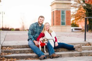 couple with their beagle dog sitting on steps in downtown Maryville for Christmas family photos