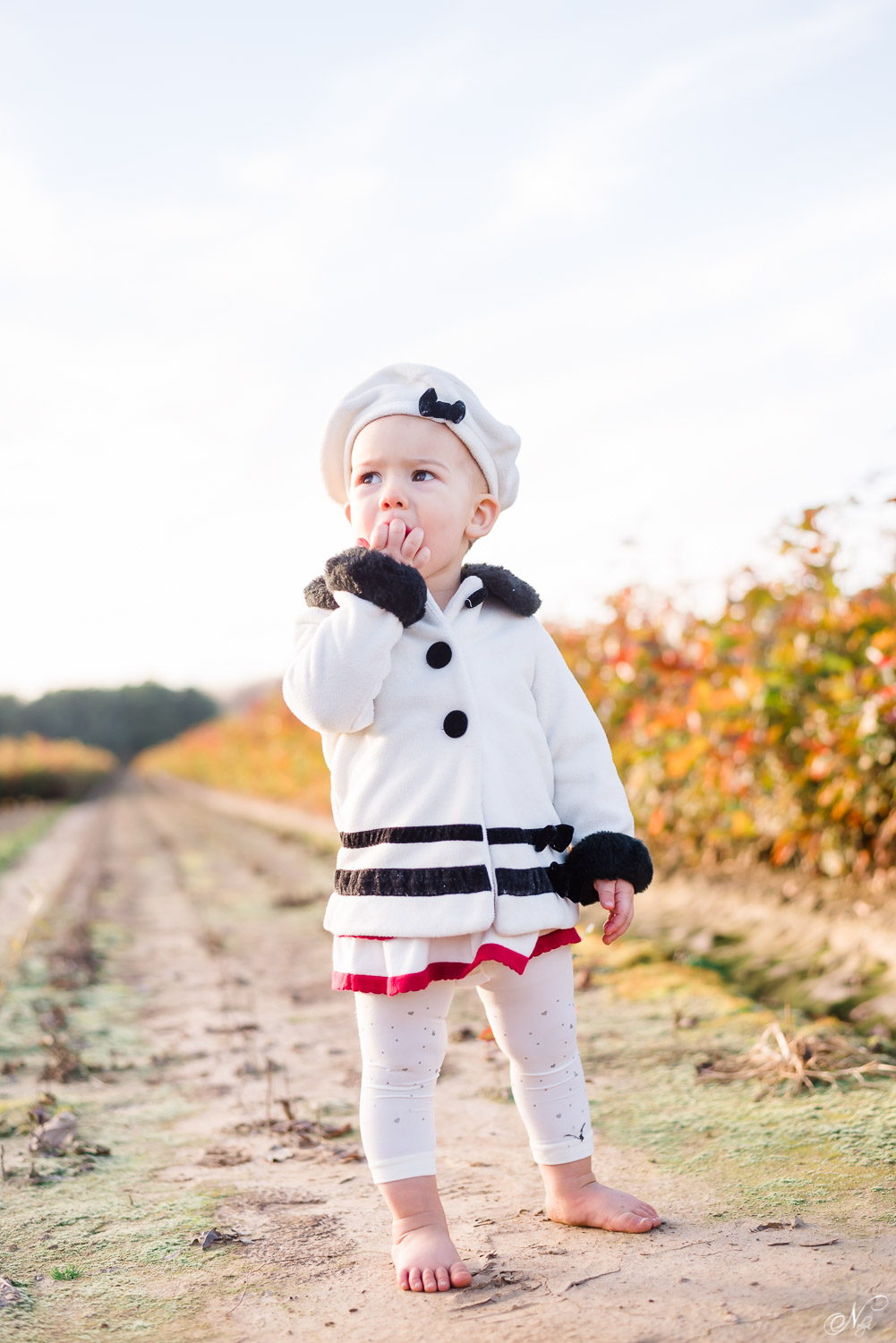 girl in white fleece coat and beret at TN nursery in Delano TN near the Hiwassee River