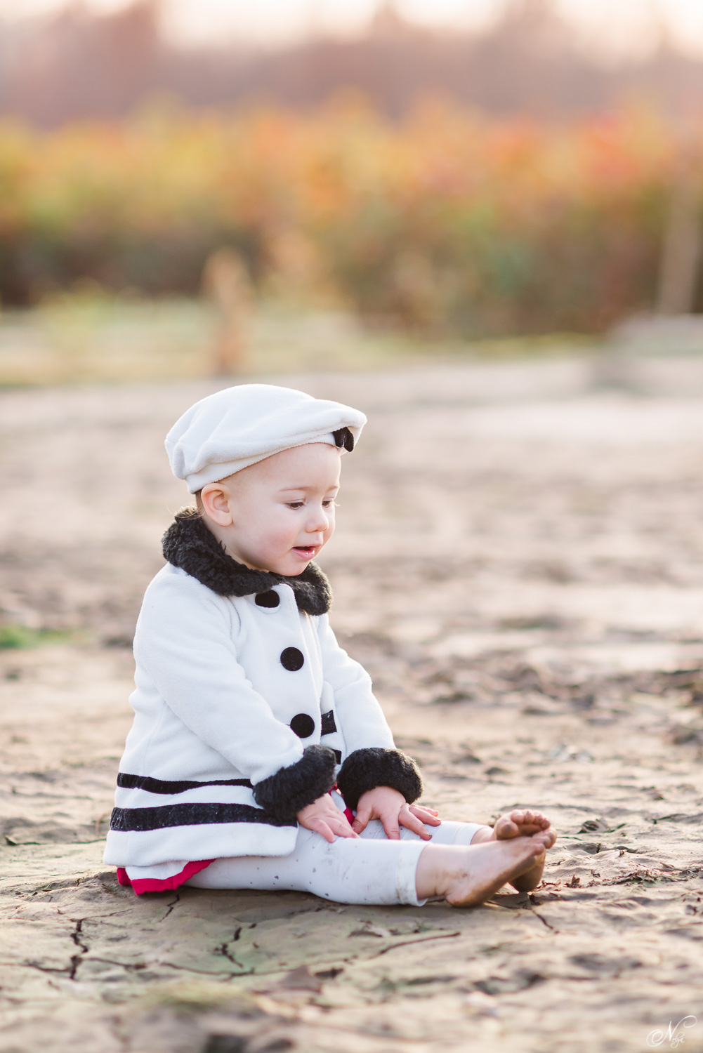 1 year old sitting in the mud in an adorable white pea coat and matching beret