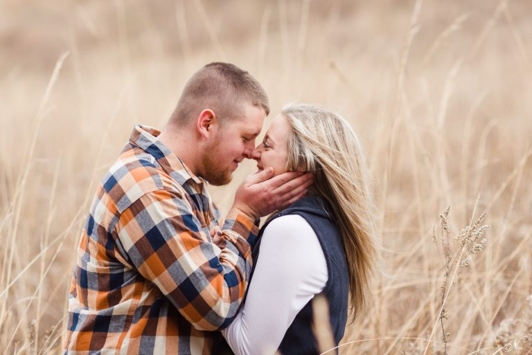 engaged couple standing in tall brown grass in Knoxville TN