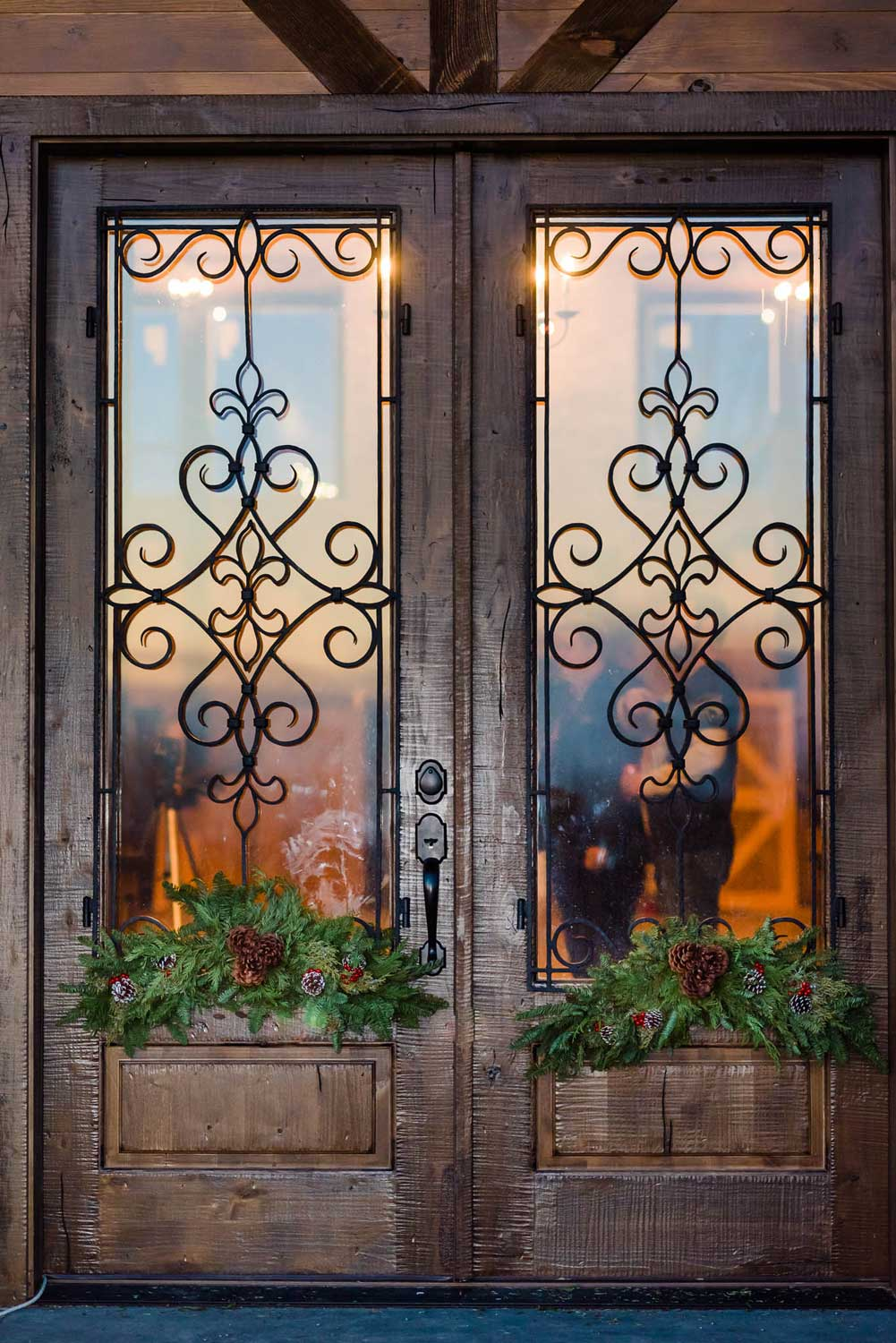 large glass and wood front doors with christmas greenery