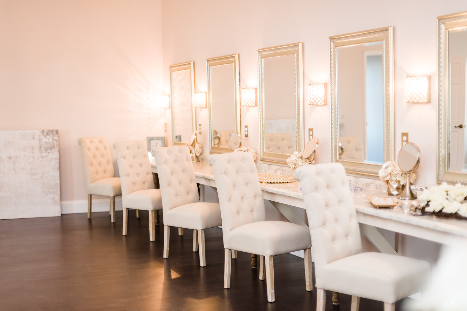 Bridal suite with six white fabric chairs and six mirrors