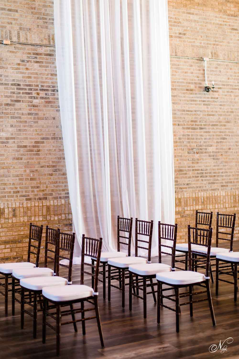 fruitwood chairs with brick wall and white draping