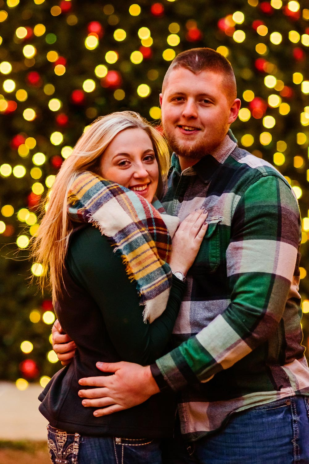 Christmas light bokeh background and smiling future mrs and mr in front. In Knoxville TN