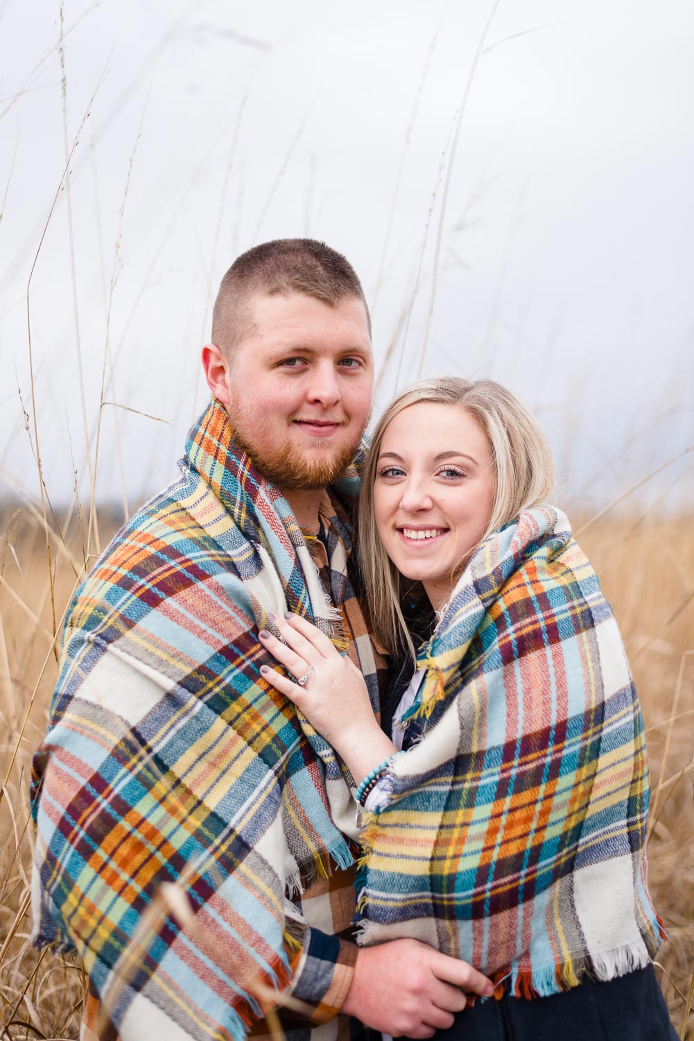 blanket scarf in plaid greens and yellows and white wrapped around couple on cold December day