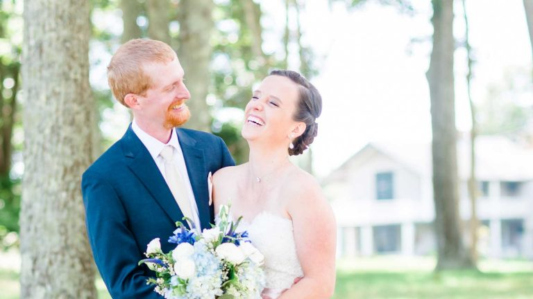 Nelya_red haired groom in blue suit and brunette bride in strapless dress outside laughing