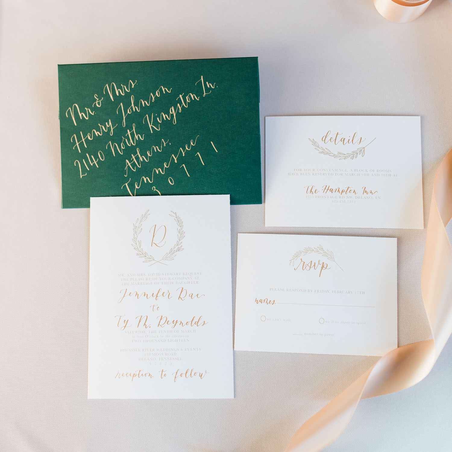wedding invitation set in white, green and gold calligraphy lettering