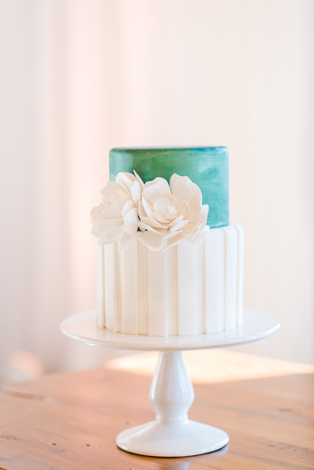 wedding cake with a huge white flower and a green top