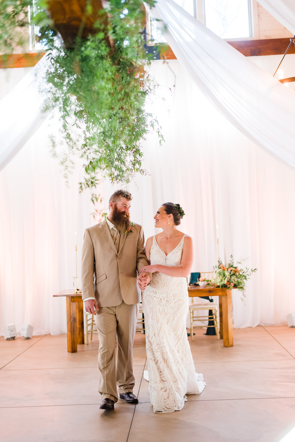 bride and groom walking into an all white draped reception at Hiwassee River Weddings