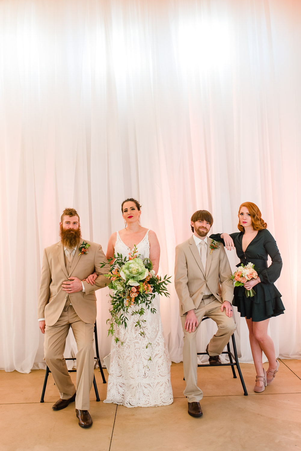 wedding party posed on tall stools in front of white draping with pink uplighting at Hiwassee river weddings