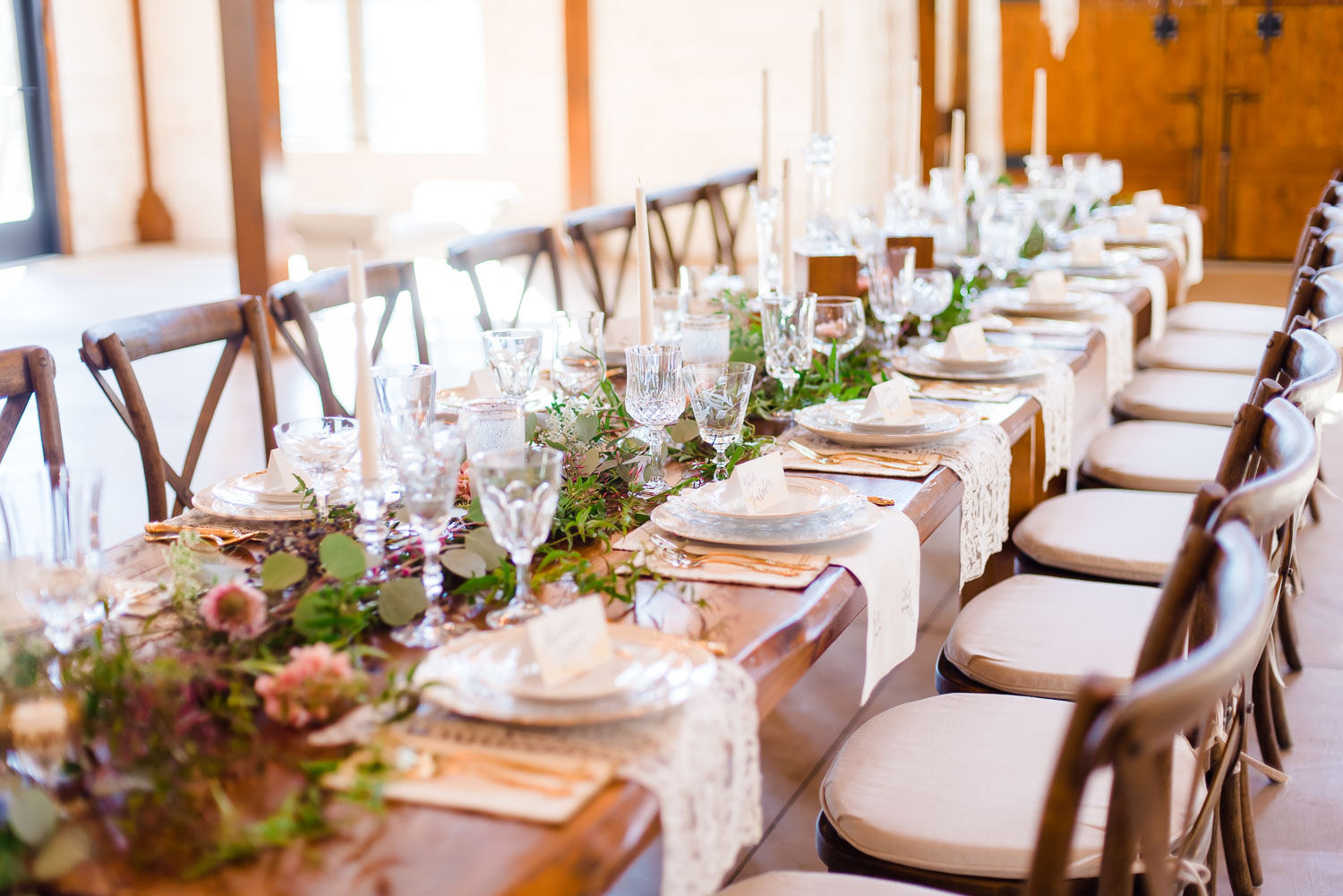 Vintage Elegance stylledplace setting with greenery center pieces on large wooden farm tables