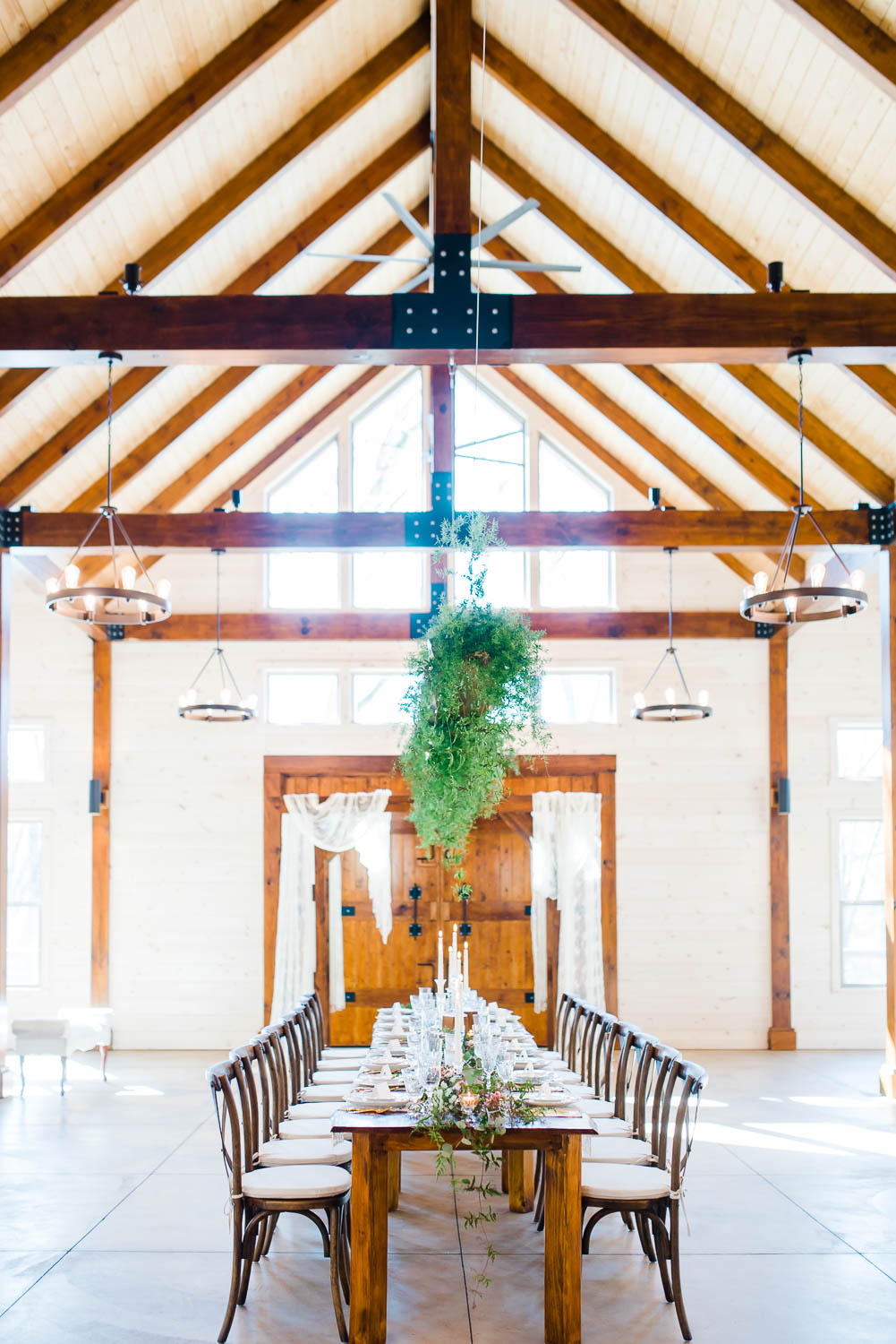 Hiwassee river weddings interior decorated with hanging greenery, crossback wooden chairs from Luma Design in Chattanooga