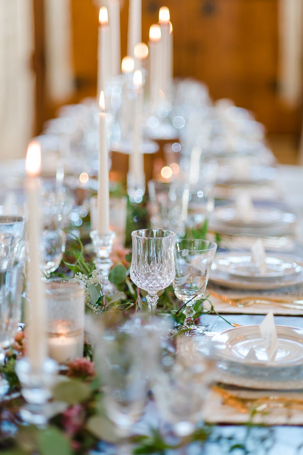 tall white candles and greenery center pieces with vintage glass goblets