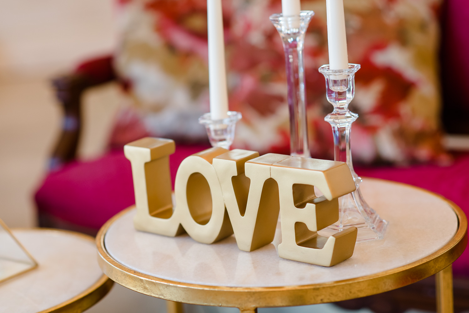 gold block decor letters spelling out LOVE and tall clear glass candle stick holders