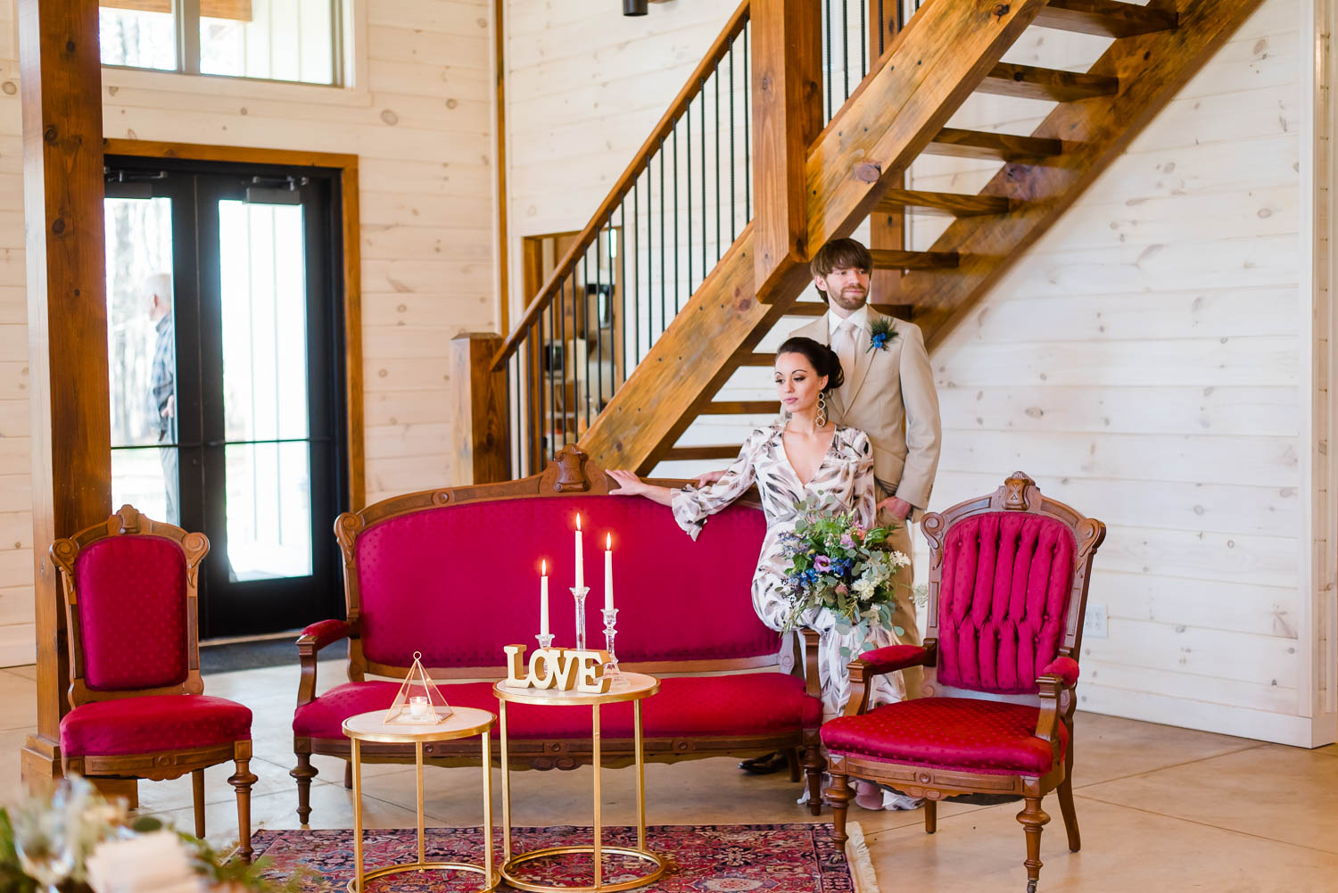 bride sitting on arm rest of red vintage couch rental from Copper Quail.