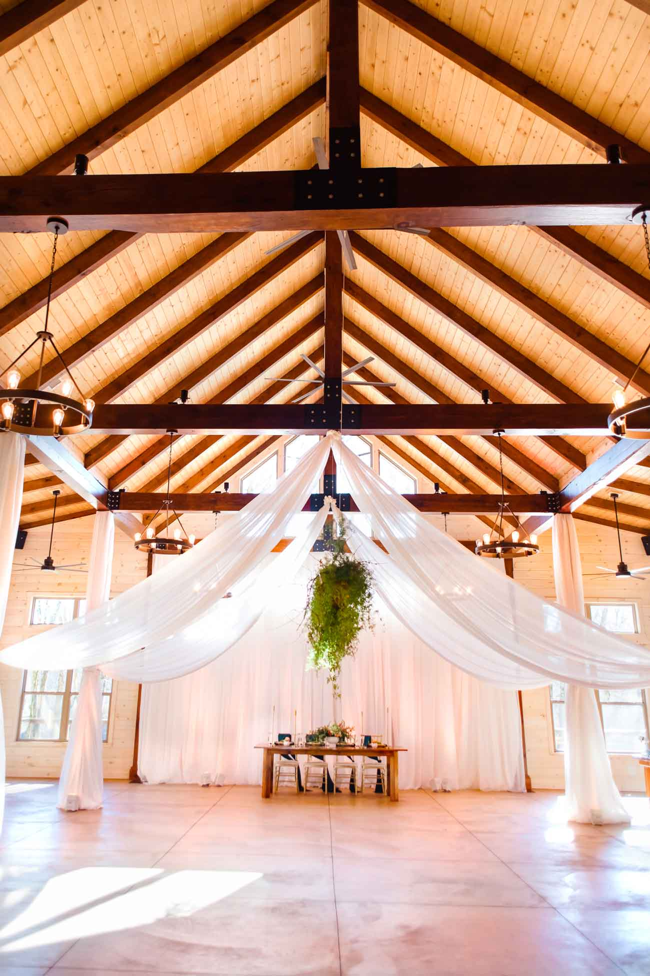 Interior of hiwassee river weddings transformed to peach and white with draping and uplighing along with hanging greenery.
