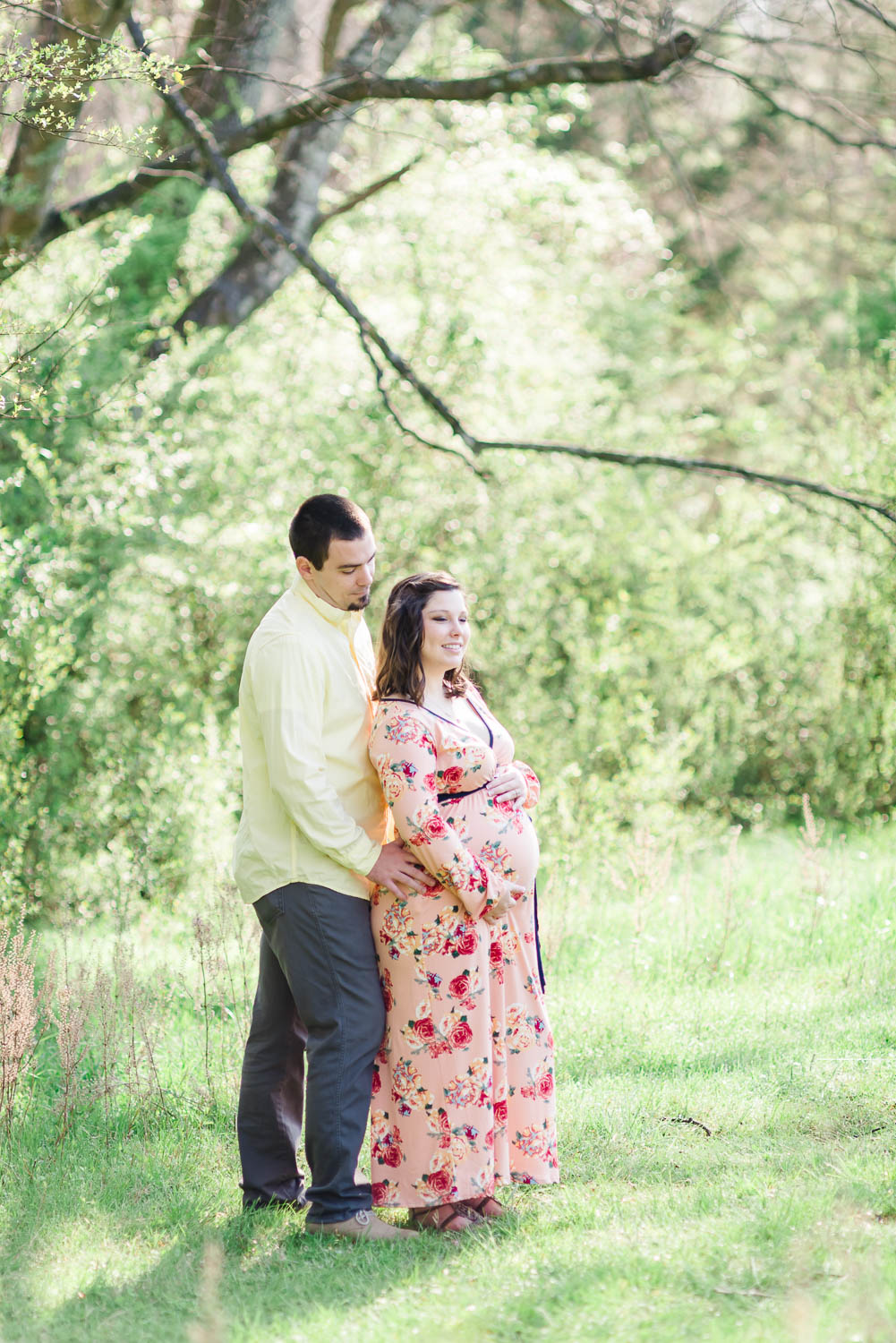 couple standing in the woods at the edge of the peach orchard near Chattanooga