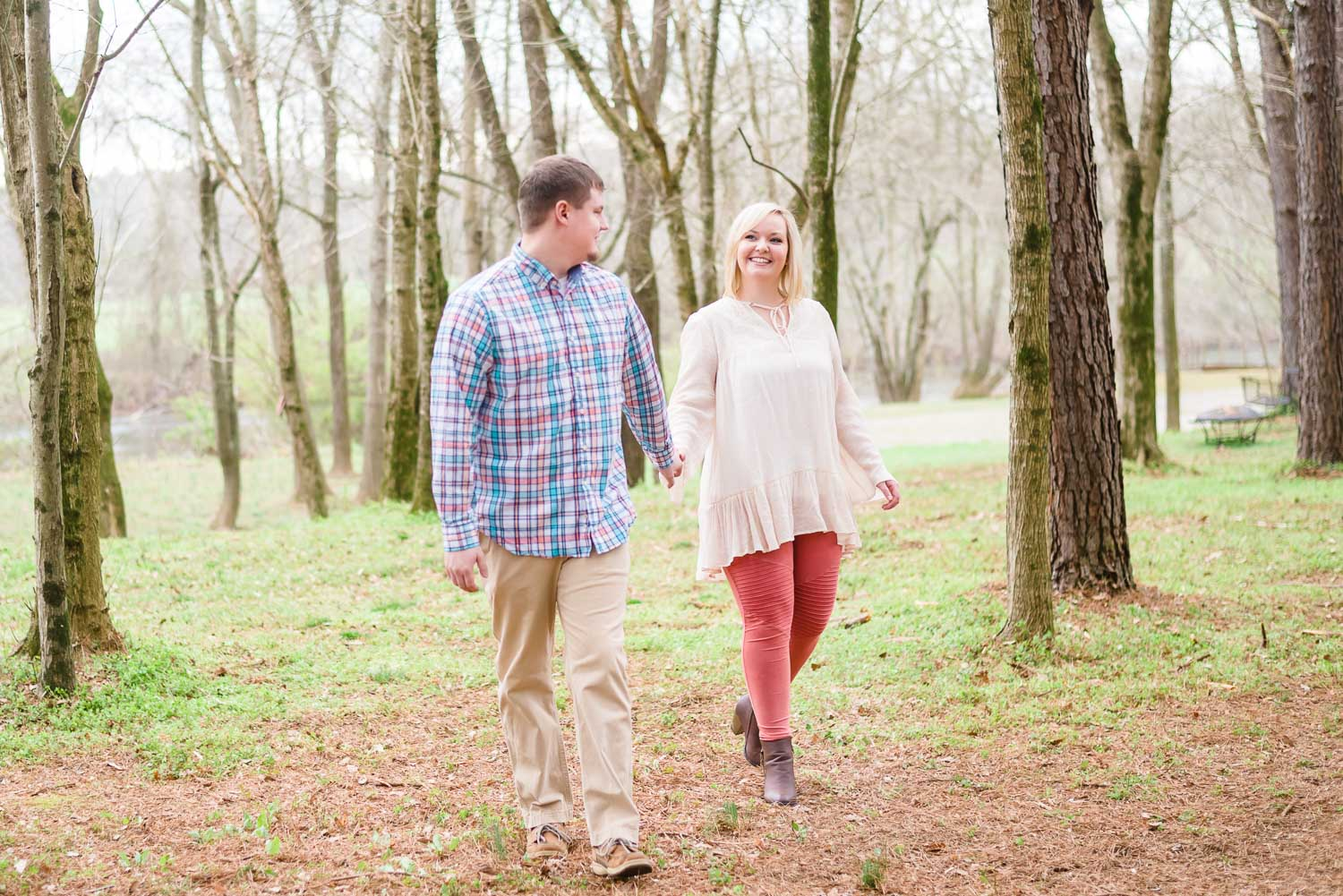 engaged couple wearing pastel themed outfits. Guy in plaied and tan pants. and girl wearing cream flowy shirt with red pants and cute ankle boots