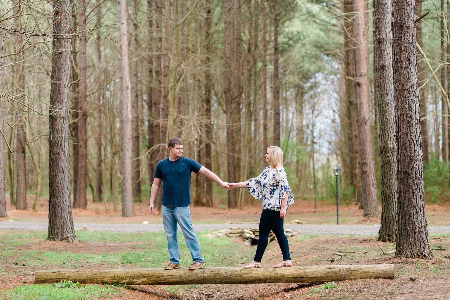 couple walking across little bridge in front of Hiwassee River wedding venue in the woods