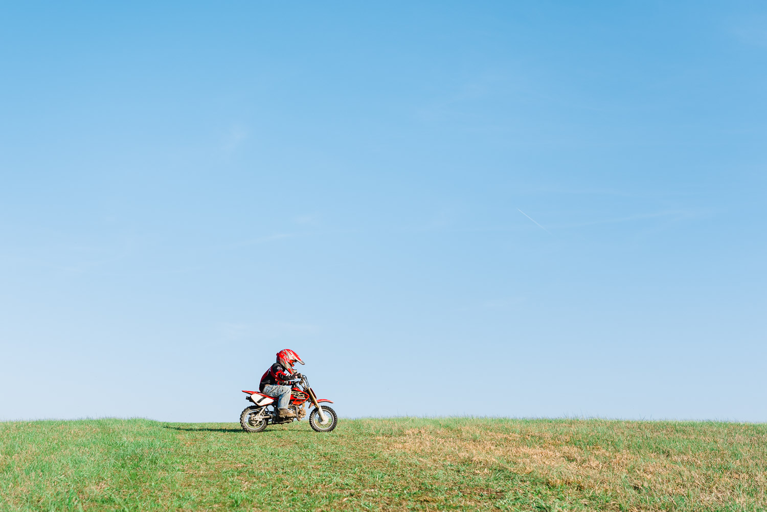 tiny honda rider riding across green grassy hill in Tennessee