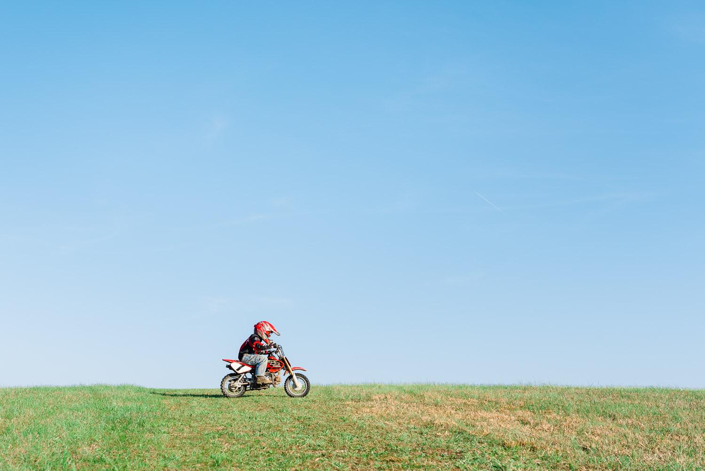 tiny honda rider riding across green grassy hill in Tennessee
