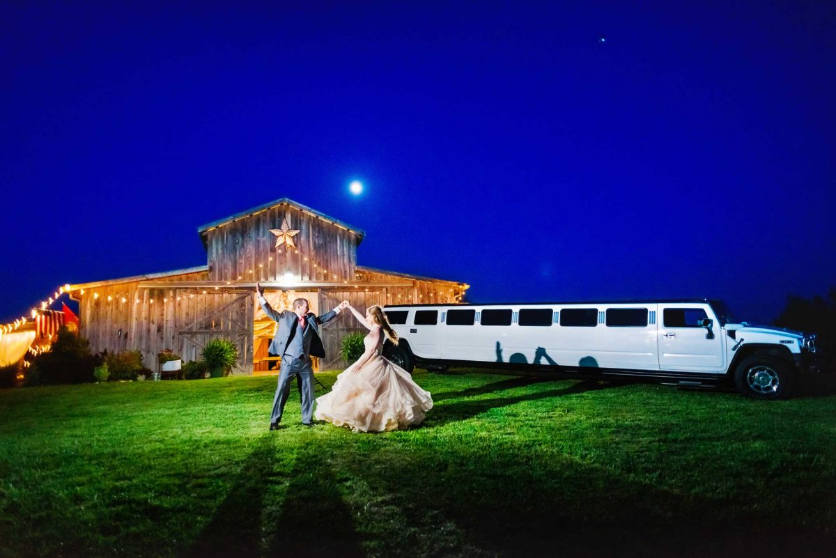 Nighttime dancing in front of the barnat drewia hill with a white hummer limo and bride and groom