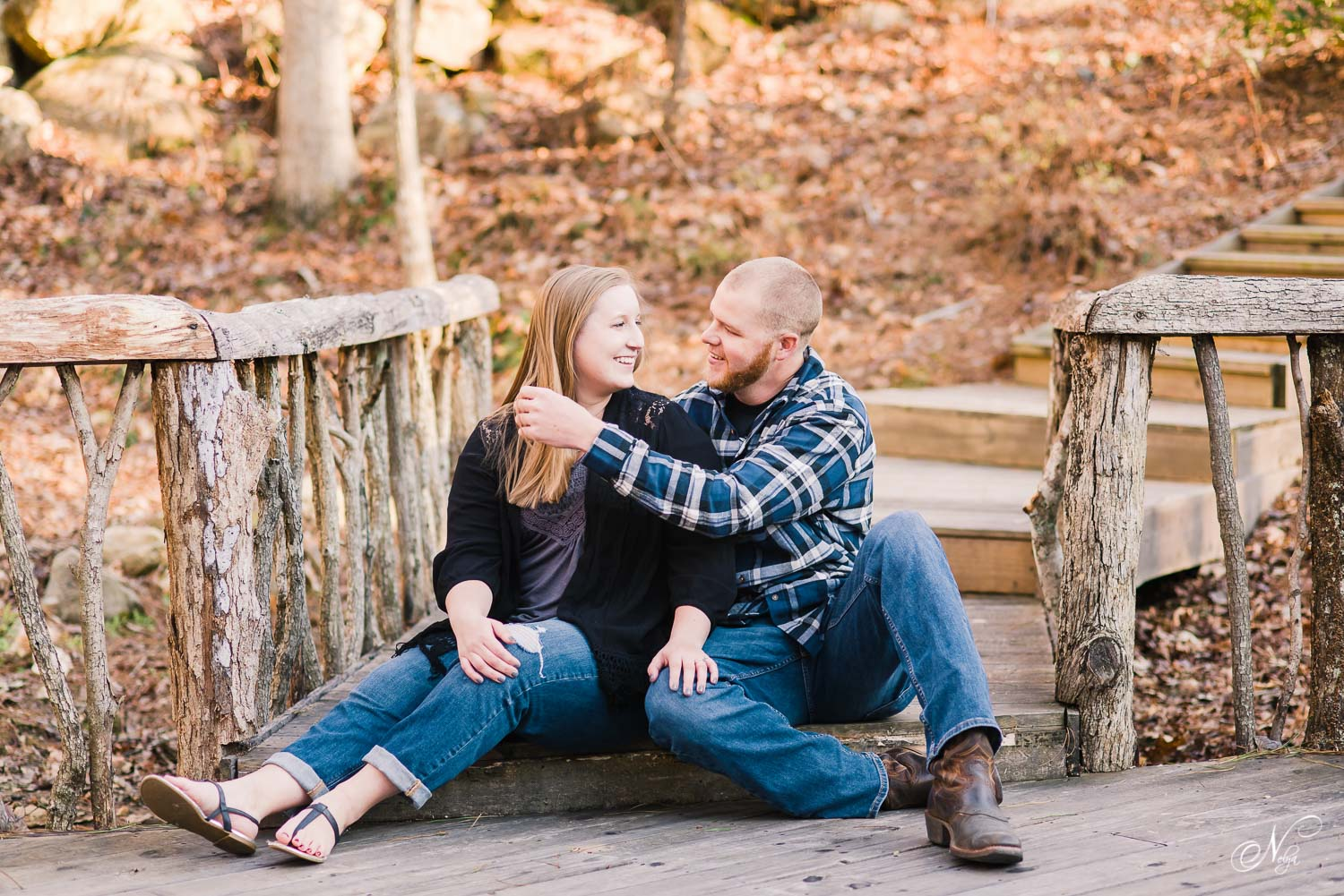 couple sitting on shady wooden walkway in West Atlanta for rustic engagement photos in the woods