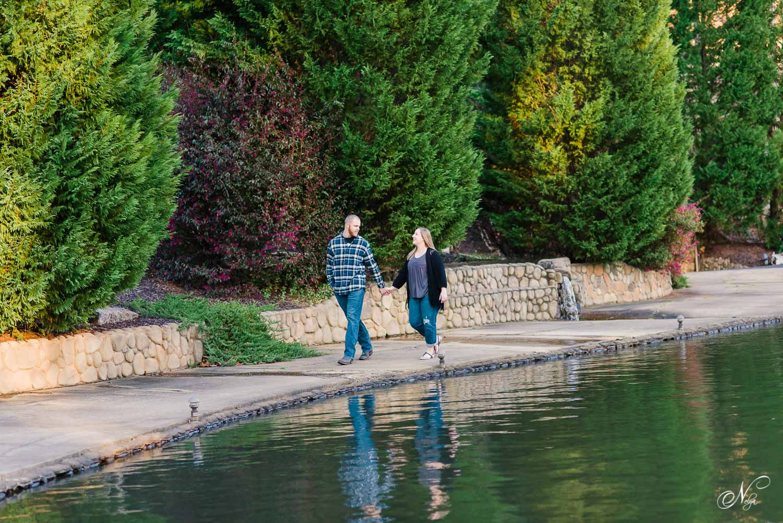 couple walking along edge of pond at Indigo Falls wedding venue
