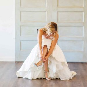 bride in wedding dress buckling her shoe in Chattanooga TN