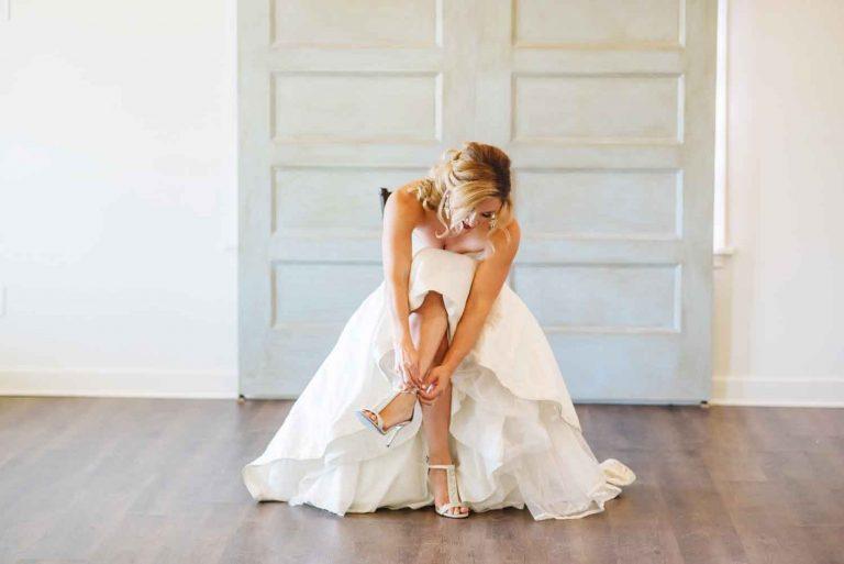 bride in wedding dress buckling her shoe in Chattanooga TN