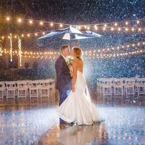 wedding couple at night in the rain under umbrella with twinkly lights in Chattanooga TN