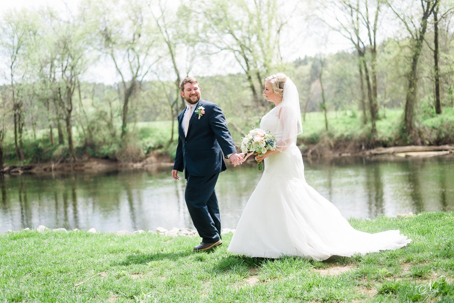 Groom looking back at his bride as they walk along the edge of the Hiwassee River in Delano TN